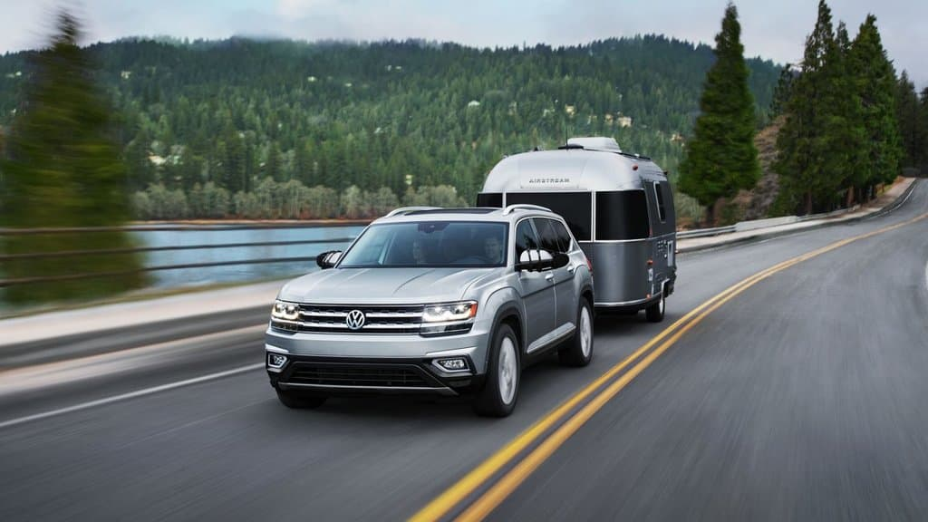 Front exterior view of the 2018 Volkswagen Atlas driving across a bridge while towing a trailer