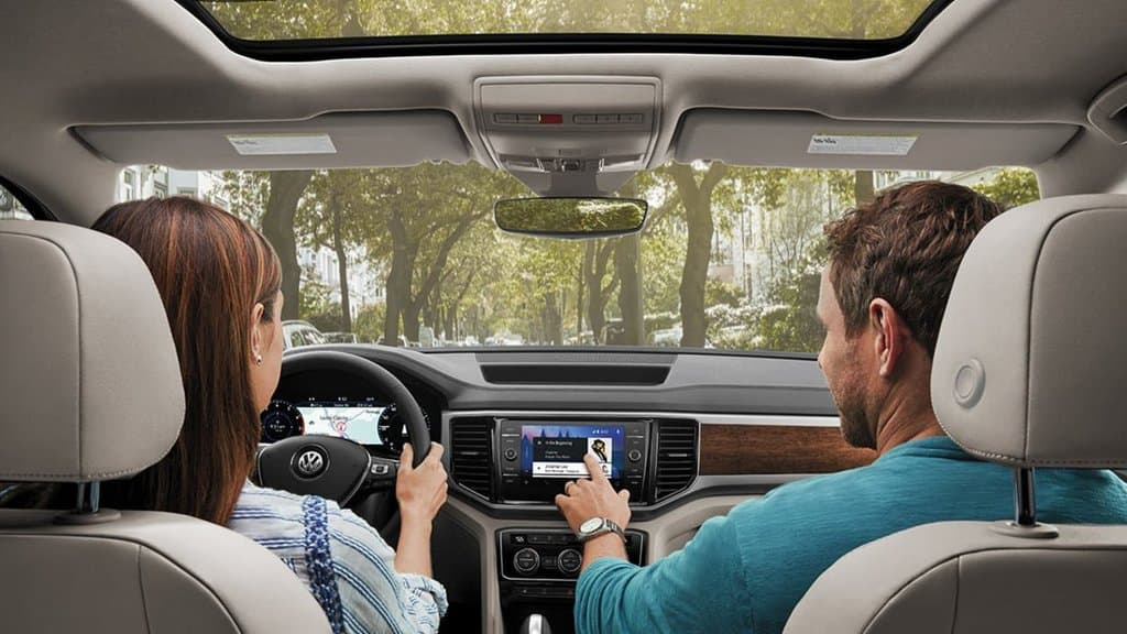 Interior view of a family inside of their 2018 Atlas using their infotainment system