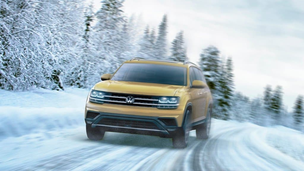 Front exterior view of the 2018 Volkswagen Atlas treading through the winter trail