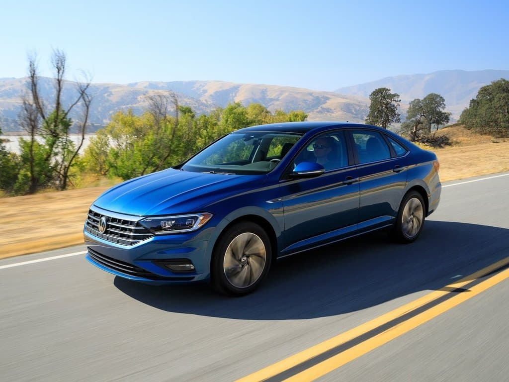 Front 3/4 exterior view of the 2019 Volkswagen Jetta driving down the highway