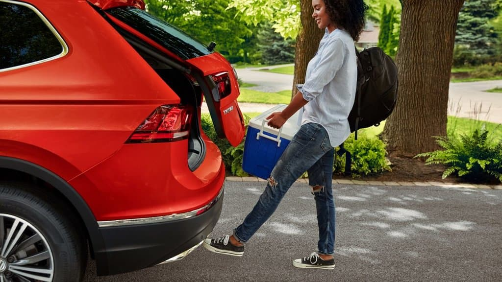 A woman loading her bags and beverage cooler into her 2018 Volkswagen Tiguan's trunk