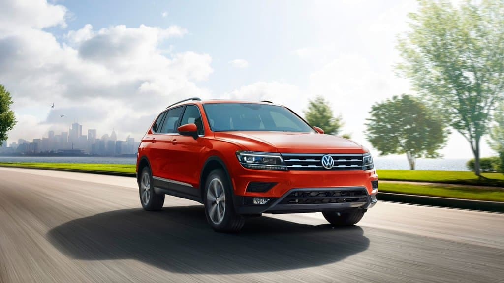 Front 3/4 exterior view of the 2018 Tiguan driving through the street